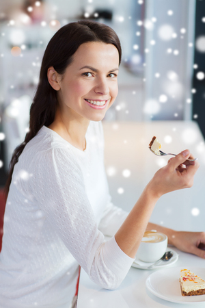 woman eating cake: leisure, drinks, people and lifestyle concept - smiling young woman eating cake and drinking coffee at cafe with snow effect