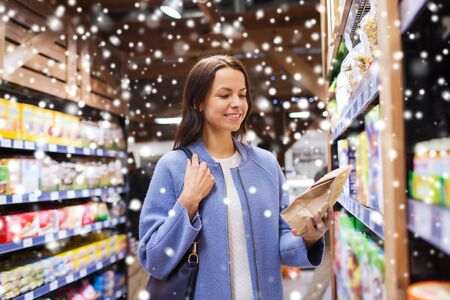 buyer: sale, shopping, consumerism and people concept - happy young woman choosing and buying food in market over snow effect Stock Photo
