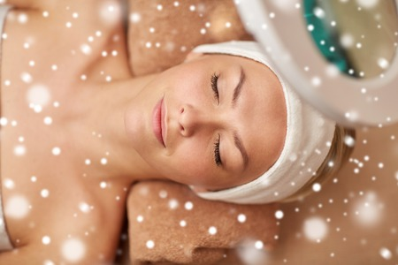 people, beauty, skin care, winter and relaxation concept - close up of beautiful young woman face with closed eyes under magnifying lamp in spa salon with snow effect