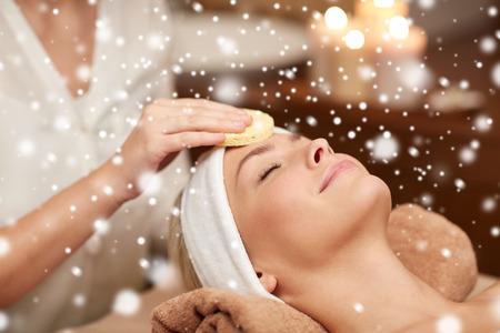 les gens, la beauté, spa, de la cosmétologie et de détente concept - close up de la belle jeune femme allongée avec les yeux fermés ayant nettoyage du visage par une éponge et de la main esthéticienne dans le spa salon avec effet de neige Banque d'images