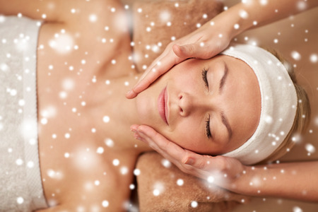 massagist: people, beauty, spa, winter and relaxation concept - close up of beautiful young woman lying with closed eyes and having face massage in spa with snow effect