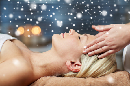 head massage: people, beauty, spa, winter and relaxation concept - close up of beautiful young woman lying with closed eyes and having face or head massage in spa with snow effect