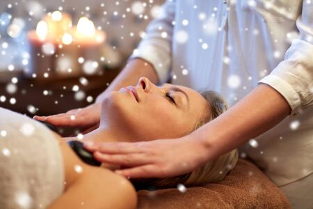 massagist: people, beauty, spa, healthy lifestyle and relaxation concept - close up of beautiful young woman having hot stone massage in spa with snow effect