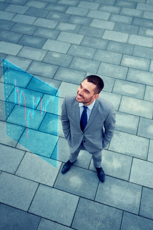 people development: business, development, finances and people concept - young smiling businessman with forex chart on virtual screen outdoors from top