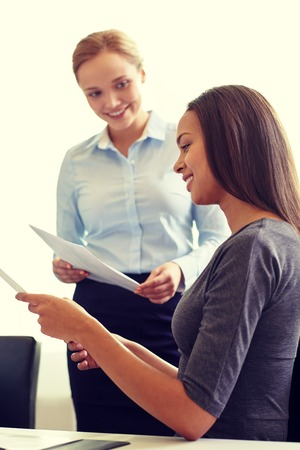 black secretary: business, people and teamwork concept - smiling businesswomen with papers talking in office