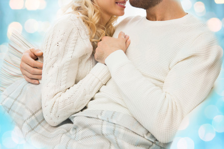 under paid: love, family, winter and happiness concept - close up of happy couple cuddling under paid at home over blue lights background Stock Photo