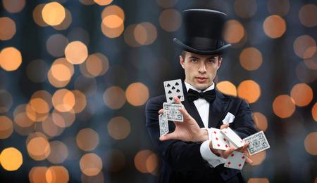 Magie, Glücksspiel, Casino, Menschen und Show-Konzept - Magier in Hut zeigt Trick mit Spielkarten über fast Lichter Hintergrund Standard-Bild - 50052763