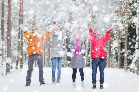 love, season, friendship and people concept - group of happy men and women having fun and playing with snow in winter forest Stockfoto