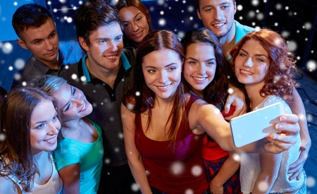 night out: party, technology, nightlife and people concept - smiling friends with smartphone taking selfie in club and snow effect Stock Photo