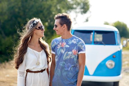 mujer hippie: vacaciones de verano, viaje por carretera, vacaciones, los viajes y el concepto de la gente - sonriente pareja hippie joven que habla sobre el coche monovolumen