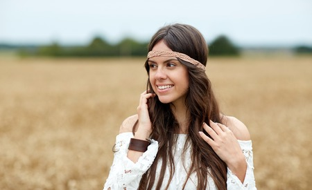 gipsy: nature, summer, youth culture and people concept - smiling young hippie woman on cereal field