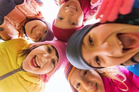 familia unida: la infancia, el ocio, la amistad y el concepto de la gente - grupo de niños felices se enfrenta en el círculo Foto de archivo