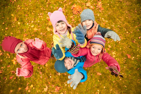 waving: childhood, leisure, friendship and people concept - group of happy children waving hands in autumn park from top