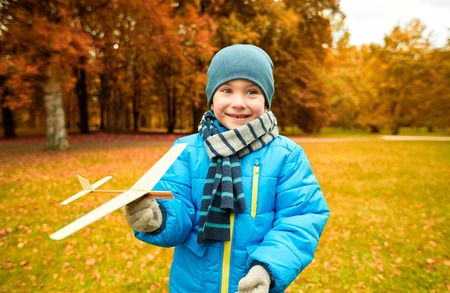 preteen model: autumn, childhood, dream, leisure and people concept - happy little boy playing with wooden toy plane outdoors