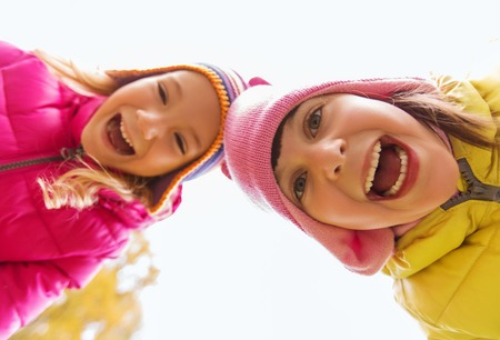 childhood, leisure, friendship and people concept - happy laughing girls faces outdoors