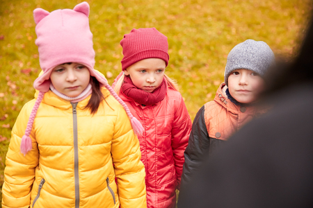 misbehavior: childhood, leisure, friendship and people concept - group of sad kids being blamed for misbehavior in autumn park