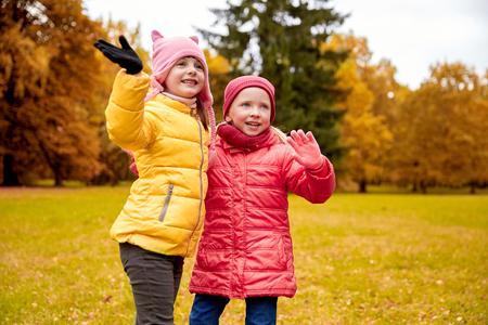 personas saludando: otoño, la infancia, el ocio y la gente concepto - dos niñas felices agitando las manos en parque del otoño Foto de archivo