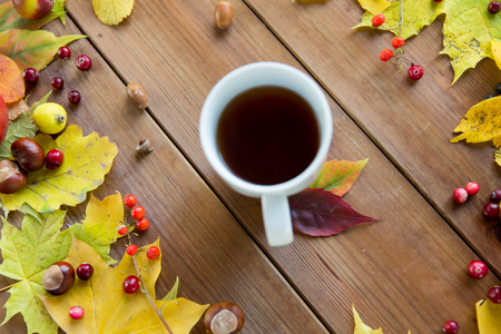 tea table: season, drink and morning concept - close up of tea cup on wooden table with autumn leaves