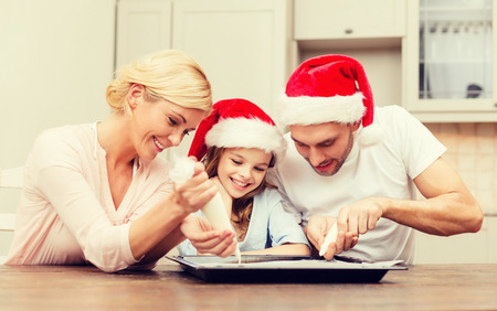 decorate: food, family, christmas, hapiness and people concept - smiling family in santa helper hats decorating cookies with glaze Stock Photo