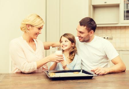 verre de lait: nourriture, famille, noël, bonheur et les gens notion - famille heureuse dans la fabrication de biscuits à la maison