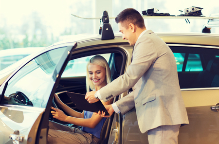 buying a car: auto business, car sale, consumerism and people concept - happy woman with car dealer in auto show or salon Stock Photo