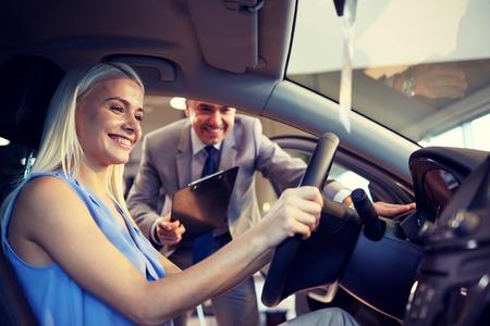 activité automobile, vente voiture, le consumérisme et les gens notion - femme heureuse avec le concessionnaire de voiture à Salon de l'auto ou un salon