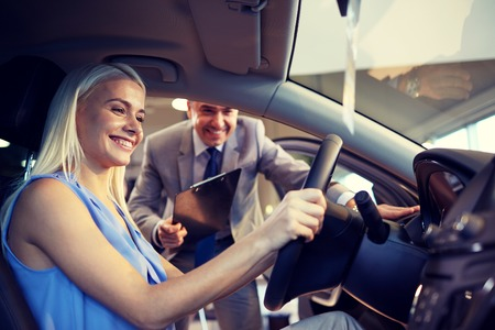 happy customer: auto business, car sale, consumerism and people concept - happy woman with car dealer in auto show or salon Stock Photo