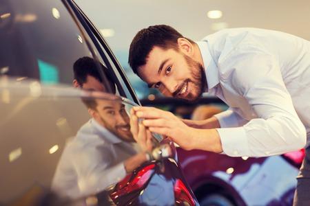 Autogeschäft, Autoverkauf, Verbraucherschutzbewegung und Leutekonzept - rührendes Auto des glücklichen Mannes in der Automobilausstellung oder im Salon