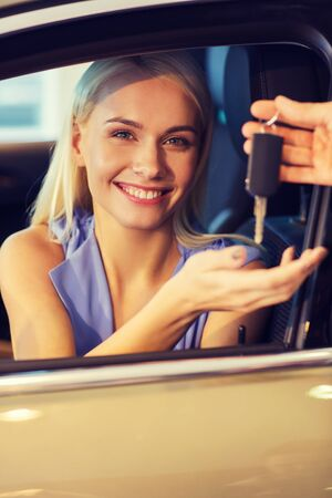 receiving: auto business, car sale, consumerism and people concept - happy woman taking car key from dealer in auto show or salon