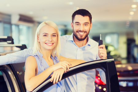 key: auto business, car sale, consumerism and people concept - happy couple buying car in auto show or salon