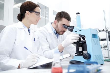 ciencia, química, tecnología, biología y concepto de la gente - los científicos jóvenes con microscopio haciendo pruebas o investigación en laboratorio clínico y tomar notas