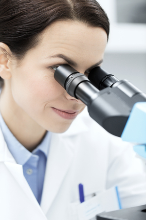 science, chemistry, technology, biology and people concept - close up of young female scientist face looking to microscope eyepiece and making or research in clinical laboratory Stock Photo - 50055074