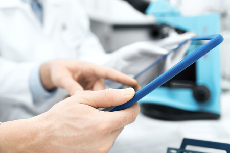 science, chemistry, technology, biology and people concept - close up of scientists hands with tablet pc in lab Stock Photo