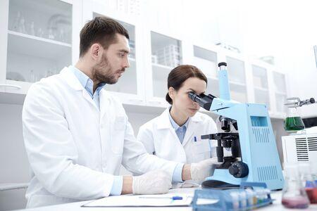 microscopio: ciencia, qu�mica, tecnolog�a, biolog�a y concepto de la gente - los cient�ficos j�venes con microscopio haciendo pruebas o investigaci�n en laboratorio cl�nico y tomar notas Foto de archivo