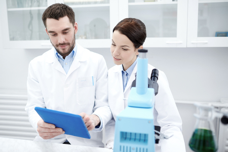 test: science, chemistry, technology, biology and people concept - young scientists with tablet pc and microscope making test or research in clinical laboratory Stock Photo