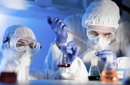 clinical laboratory: science, chemistry, biology, medicine and people concept - close up of young scientists with pipette and flasks making test or research in clinical laboratory