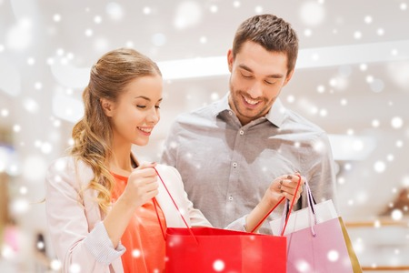 sale, consumerism and people concept - happy young couple showing content of shopping bags in mall with snow effect Foto de archivo