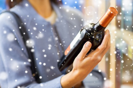 sale, shopping,  holidays, consumerism and people concept - happy young woman choosing and buying wine in market or liquor store over snow effect