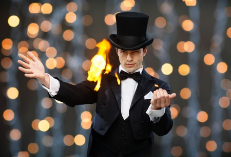 conjuring: magic, performance, circus, people and show concept - magician in top hat showing trick over nigh lights background Stock Photo