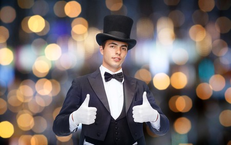 conjuring: magic, performance, gesture people and show concept - magician in top hat showing thumbs up over nigh lights background