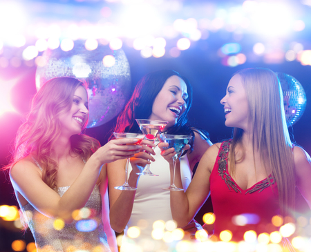 party time: holidays, nightlife, bachelorette party and people concept - smiling women with cocktails at night club Stock Photo