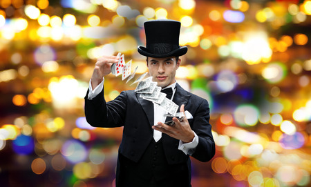 magician hat: magic, gambling, casino, people and show concept - magician in top hat showing trick with playing cards over nigh lights background