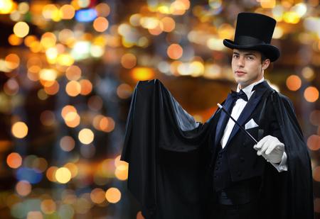 mago: rendimiento, circo, espectáculo concepto - mago en el sombrero de copa y capa mostrando truco con la varita mágica sobre fondo luces cerca Foto de archivo