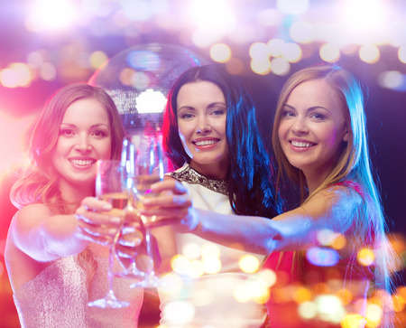 holidays, nightlife, bachelorette party and people concept - smiling women with champagne glasses at night club Фото со стока
