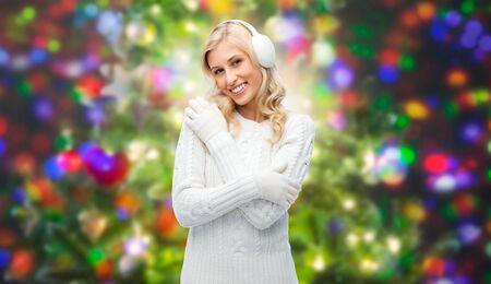 diciembre: invierno, la moda, la Navidad y la gente concepto - mujer joven sonriente en las orejeras y suéter sobre las vacaciones luces de fondo