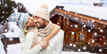 snow woman: winter, vacation, couple, christmas and people concept - smiling man and woman in hats and scarf hugging over wooden country house and snow background Stock Photo