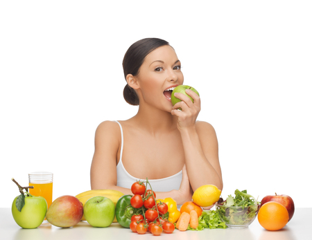 woman eating apple with lot of fruits and vegetables Stockfoto