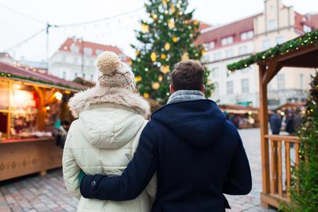 espalda: concepto de fiesta, invierno, navidad, el turismo y la gente - cerca de la pareja en el casco antiguo de la parte posterior