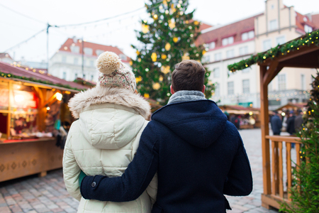 back to back couple: holidays, winter, christmas, tourism and people concept - close up of couple in old town from back