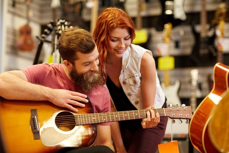 young musician: music, sale, people, musical instruments and entertainment concept - happy couple of musicians with guitar at music store